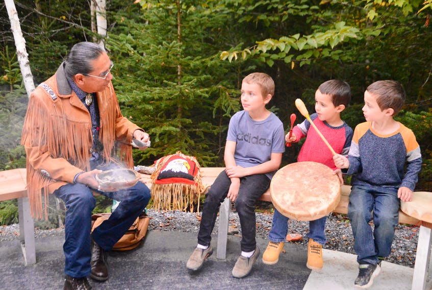 Revered and respected Mi'kmaq elder Stephen Augustine burns sage while sharing his knowledge with youngsters, from left, Reece Bagnell, 6, Benjamin Chisholm, 4, and his brother Jacob Chisholm, 6. The Hereditary Chief of the Mi'kmaq Grand Council took part in the official opening ceremony of Riverside Elementary School's new Knowledge Path. DAVID JALA/CAPE BRETON POST
