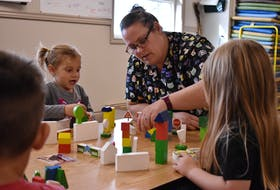 Kellie Davies, vice-president of operations for Milestones Early Learning Centre in Stratford, plays with some of the children at the centre on Sept. 28. The children, from left, are Thatcher, Maria and Sadie. The centre did not disclose the children's last names.