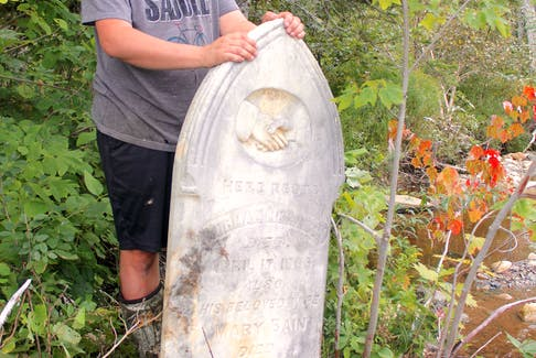 """Jeffrey Parks, a 26-year-old antique dealer from Middle River, stands beside a headstone he lifted after it had fallen down an eroding embankment into the Baddeck River this spring. """"I hate the idea of being forgotten and this is terrifying to me. I don't want to end up like this,"""" he said. CHRIS CONNORS/CAPE BRETON POST"""