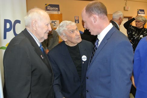 Former Nova Scotia premiers John Buchanan, left, and Roger Bacon, centre, speak to Cumberland South MLA Tory Rushton during a nominating meeting in 2018.