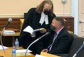 George Pottle (seated), a lieutenant with the St. John's Regional Fire Department, speaks with his defence lawyer, Bob Buckingham, during a break in his trial at Newfoundland and Labrador Supreme Court in St. John's Tuesday morning, Oct. 5. Pottle has pleaded not guilty to assaulting and threatening a woman in April 2018.