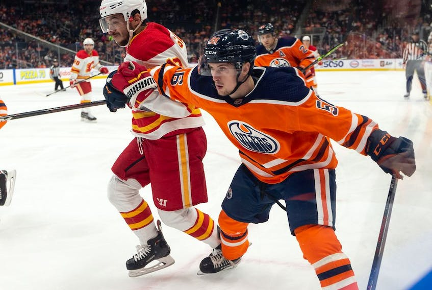 Edmonton Oilers' Kailer Yamamoto (56) battles Calgary Flames' Johnny Gaudreau (13) during second period preseason NHL action at Rogers Place in Edmonton, on Monday, Oct. 4, 2021.