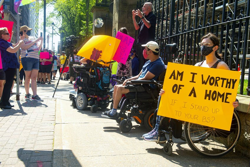 April Hubbard holds a sign as she attends a Disability Rights Coalition rally outside Province House on Friday, Aug. 13, 2021.