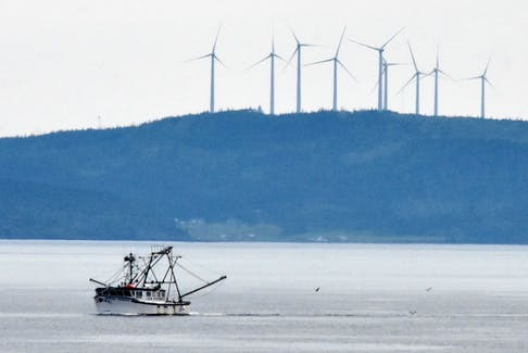 A fishing vessel sails by with wind turbines in Digby County in the background. A wind farm is being proposed for Sandy Point, Shelburne County. TINA COMEAU • TRICOUNTY VANGUARD
