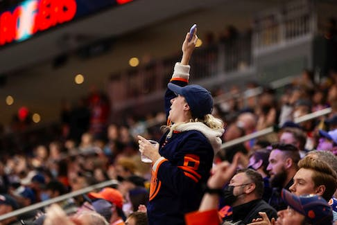 Edmonton Oilers fans cheer Connor McDavid's goal on Calgary Flames' goaltender Jacob Markstrom (25) during third period preseason NHL action at Rogers Place in Edmonton, on Monday, Oct. 4, 2021.