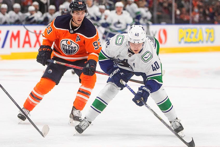 Vancouver Canucks' Elias Pettersson, right, is hooked Edmonton Oilers' Ryan Nugent-Hopkins during first-period pre-season action in Edmonton on Oct. 7.