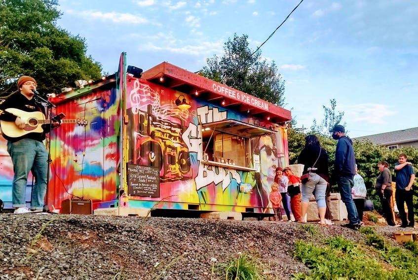 Musician Landon Morris, left, performed outside the GrooveBox on Granville in Port Hawkesbury this past summer as customers lined up for ice cream and coffee. The seasonal business is located in a used shipping container. CONTRIBUTED