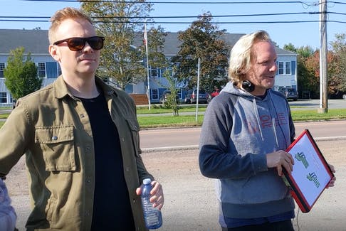 Nathan Macintosh, at left, standing with Jonathan Torrens while he debriefs the crew during a set change outside the Valley Variety store.
