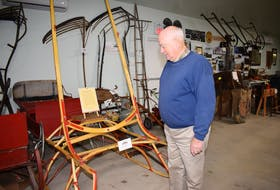 Page Baird, long-serving volunteer and chairman of the Farm Equipment Museum in Bible Hill shows a visitor a sleigh that he rebuilt, one of numerous items he has refurbished at the facility.