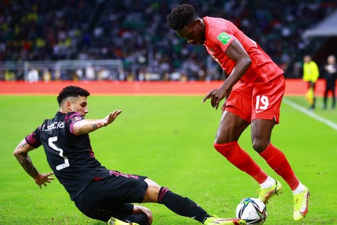 Jorge Sanchez of Mexico battles for possesion with Alphonso Davies of Canada during the match between Mexico and Canada as part of the Concacaf 2022 FIFA World Cup Qualifier at Azteca Stadium on October 07, 2021 in Mexico City, Mexico.