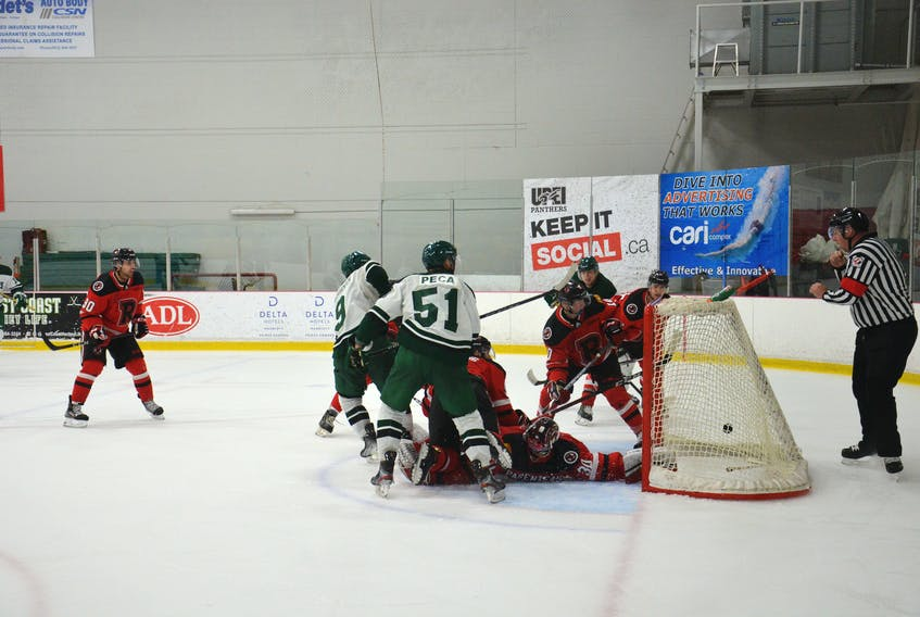 Kyle Maksimovich, 9, bangs home a rebound during a scramble around UNB Reds goaltender Rylan Parenteau with eight seconds remaining in regulation time to lift the UPEI Panthers into a 2-2 tie. UNB won the Atlantic University Sport men's hockey game, played at MacLauchlan Arena, 3-2 in overtime.