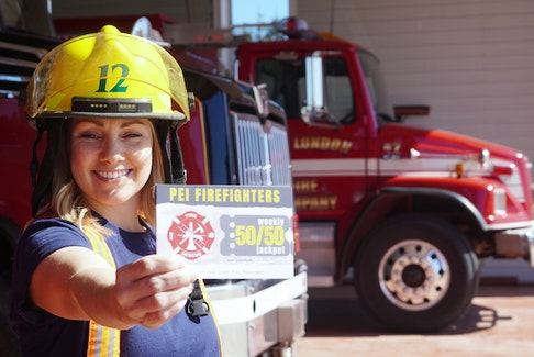 Angie Arsenault, a volunteer firefighter with the New London Fire Department, holds a promotional card for a weekly P.E.I. fundraiser.