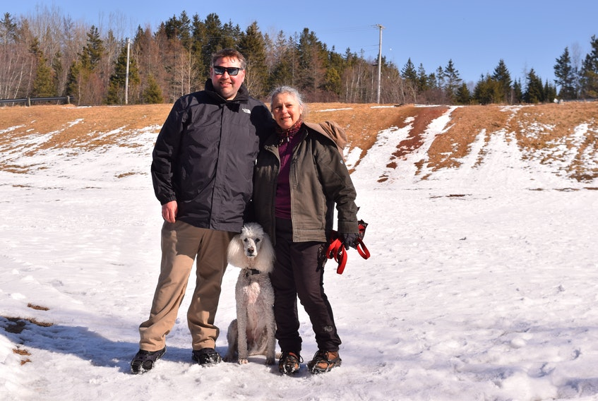 Scott Hagell, left, and Ginny Hingley with their furry friend, Addison, on the field. Hingley has spearheaded efforts to develop the area as a green space.
