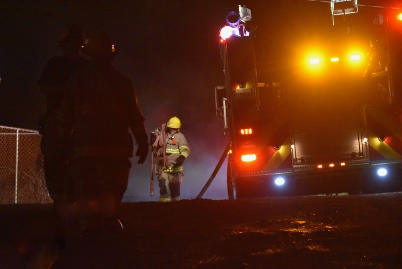 A firefighter carries a hose back to a truck following a barn fire in Chebogue, Yarmouth County, on the evening of March 23. The Yarmouth Fire Department responded to the call, which also required mutual aid assistance from other departments. TINA COMEAU PHOTO