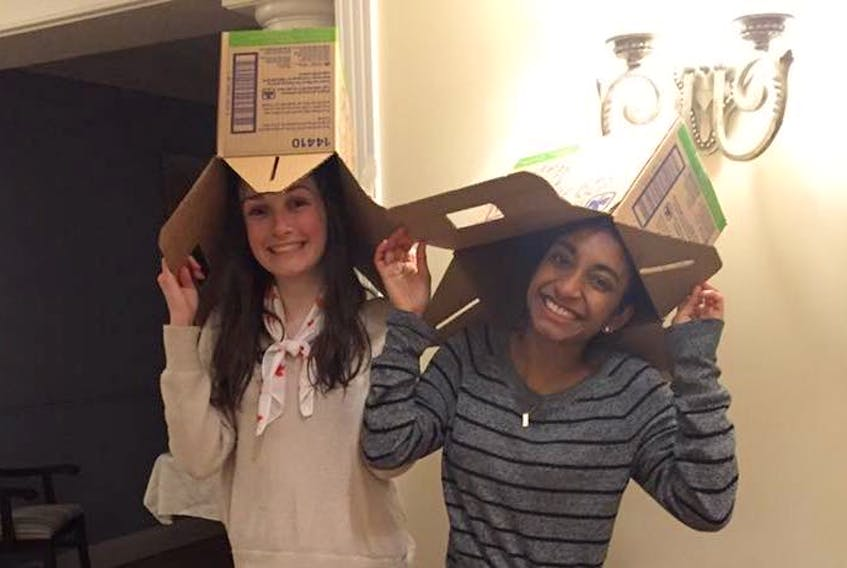 Former Rangers Laura Murphy (left) and Viraji Rupasinghe have fun with a few empty cookie cases. The goal will be to empty a bunch of cases this Saturday during the drive-thru sale.
