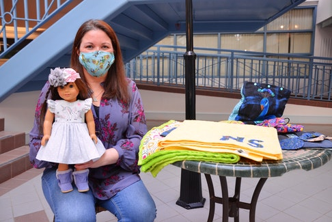 Fabric & Flour owner Kelly Dolan with one of the doll dresses, and several other unique items, that she is now offering. KIRK STARRATT