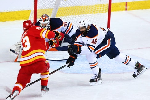 Calgary Flames forward Sam Bennett gets a shot on Edmonton Oilers goaltender Mike Smith and as Oilers defenceman Jujhar Khaira reaches in during NHL action at the Scotiabank Saddledome in Calgary on Saturday, April 10, 2021.   Gavin Young/Postmedia
