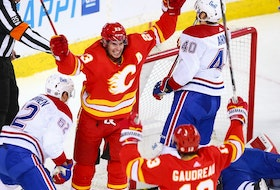 Calgary Flames forward Sean Monahan celebrates with Johnny Gaudreau after scoring on Montreal Canadiens goaltender Carey Price at the Saddledome in Calgary on Saturday, March 13, 2021.
