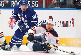 Connor McDavid of the Edmonton Oilers battles for the puck against Auston Matthews of the Toronto Maple Leafs at Scotiabank Arena on March 29, 2021 in Toronto.
