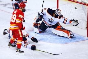 Calgary Flames forward Sean Monahan's shot sails into the net past Edmonton Oilers goaltender Mike Smith at the Scotiabank Saddledome in Calgary on Saturday, April 10, 2021.