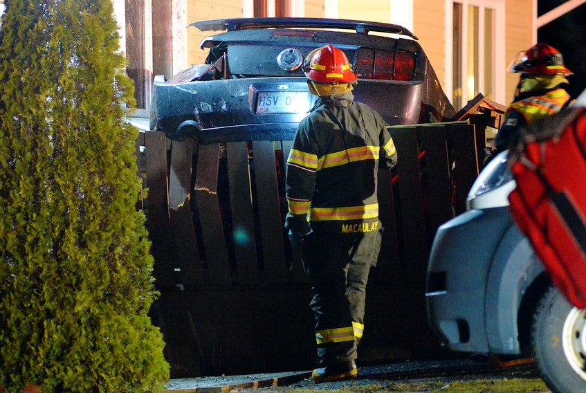 Firefighters check on a car that crashed into two vehicles and a house after it went airborne during a crash Sunday night in Torbay. Keith Gosse/The Telegram