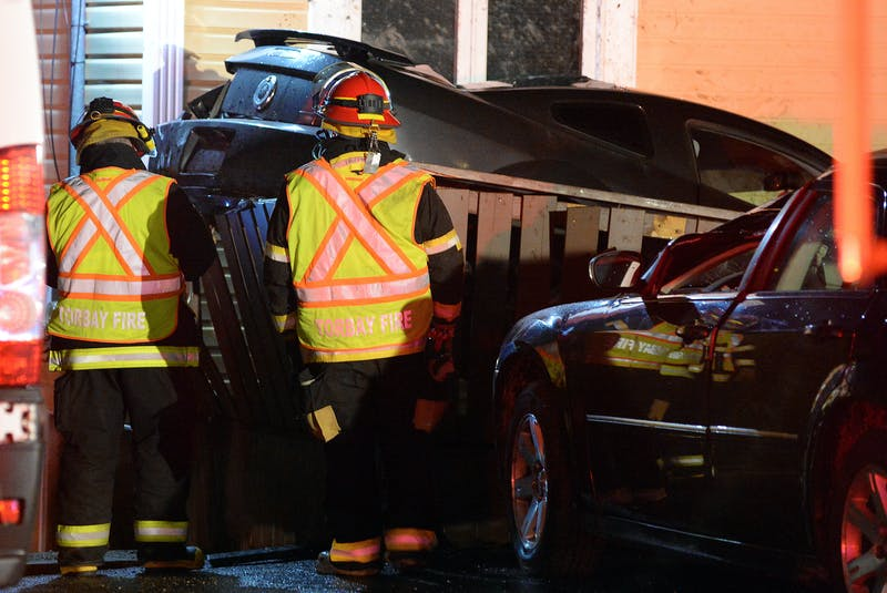 Firefighters check on a car that crashed into two vehicles and a house after it went airborne during a crash Sunday night in Torbay. Keith Gosse/The Telegram - Keith Gosse