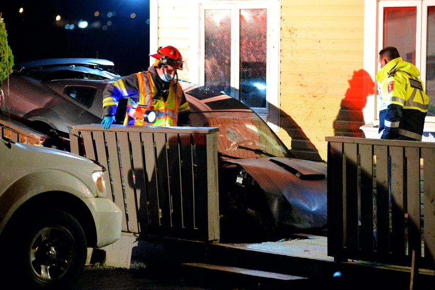A firefighter and a paramedic check on a car that crashed into two vehicles and a house after it went airborne during a crash Sunday night in Torbay. Keith Gosse/The Telegram