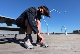 April 12, 2021 - Adrian Delli Colli laces up his running shoes along the Halifax boardwalk Monday afternoon. Delli Colli is helping organize Sunday's Nova Scotia Remembers Memorial Road Race to honour the memories and families of the victims of the mass shooting, which happened one year ago on April 18 and 19.