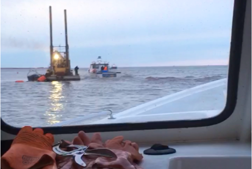 The dredger, seen here from inside Chris Wall's boat, is on site at Malpeque harbour, though Wall didn't know if dredging had started yet.