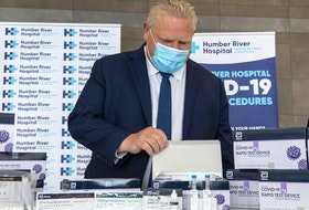Ontario Premier Doug Ford examines COVID-19 Rapid Test Device kits at Humber River Hospital in Toronto on Nov. 24, 2020.