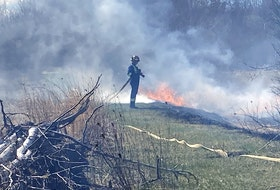A Port Williams firefighter waits for water to arrive at his nozzle while fighting a grass fire that started as an illegal fire.