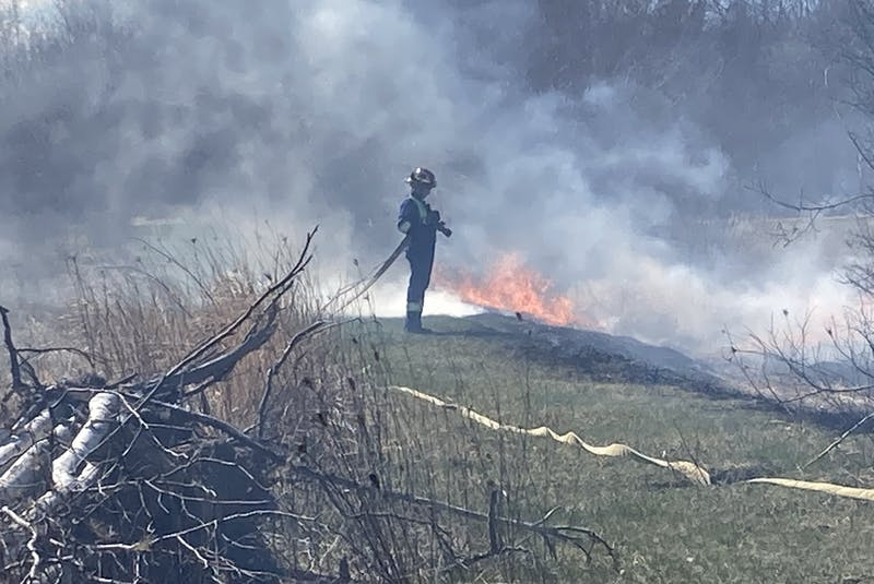 A Port Williams firefighter waits for water to arrive at his nozzle while fighting a grass fire that started as an illegal fire. - Ian Fairclough