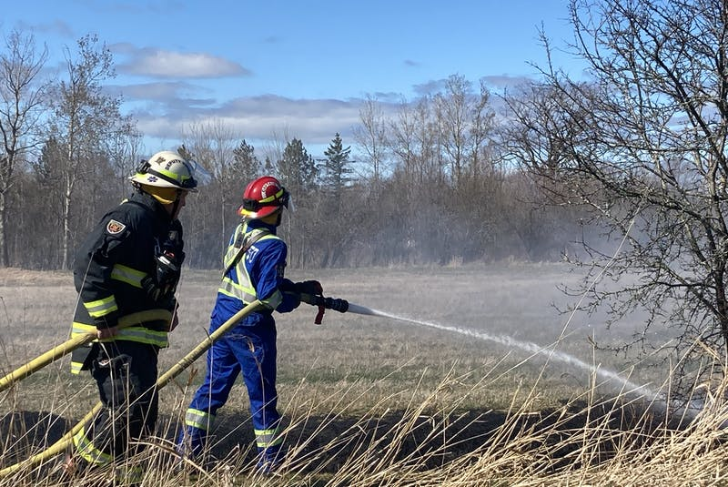 Port Williams firefighters work to extinguish a grass fire that started from a fire that was started at a time of day when it could not legally be lit. - Ian Fairclough