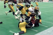 Edmonton Football Team defensive back Don Wilson (25) hits the pile to bring down Calgary Stampeders ball carrier Kelvin Anderson (32) in the West Division final on Nov. 14, 1998.