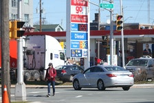 A man walks across Young Street as a car prepares to make a left-hand turn from Kempt Road in Halifax Monday April 12, 2021. Coun. Waye Mason wants the municipality to consider options for establishing protected left-turn and right-turn movements at intersections with high traffic and pedestrian volumes like the Young Street and Kempt Road intersection, where David Gass was struck by a vehicle last month and died of his injuries shortly after.