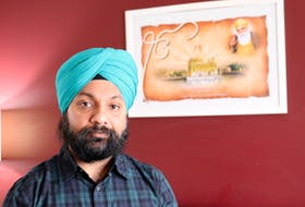 Savneet Singh Malhotra stands in front of a picture of the Harmandir Sahib – or Golden Temple – a gurdwara in India which serves free meals to 100,000 people each day.