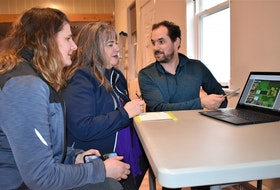 Erin MacKinnon (left), Alana Hirtle and Andrew MacDonald of the Rotary Care Committee go over plans for major improvements to the Portapique Community Hall. The work and hall enhancements are seen as a way for the community to heal following the mass shootings last April.