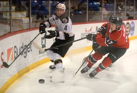 Charlottetown Islanders rookie Ryan Maynard, left, flips the puck behind the Halifax Mooseheads net while being defended by defenceman Cam Whynot Tuesday at the Eastlink Centre in Charlottetown.