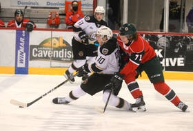 Charlottetown Islanders captain Brett Budgell, left, tries to get the puck to a teammate while fending off the check of Halifax Mooseheads centre Attilio Biasca Tuesday at the Eastlink Centre in Charlottetown.