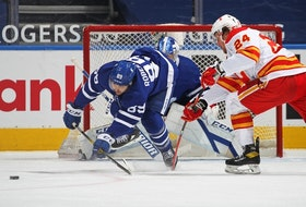 Maple Leafs forward Nick Robertson (left) clears the puck against the Calgary Flames on Tuesday night at Scotiabank Arena. Robertson was placed on the list of NHL players who are unavailable because of COVID protocol.