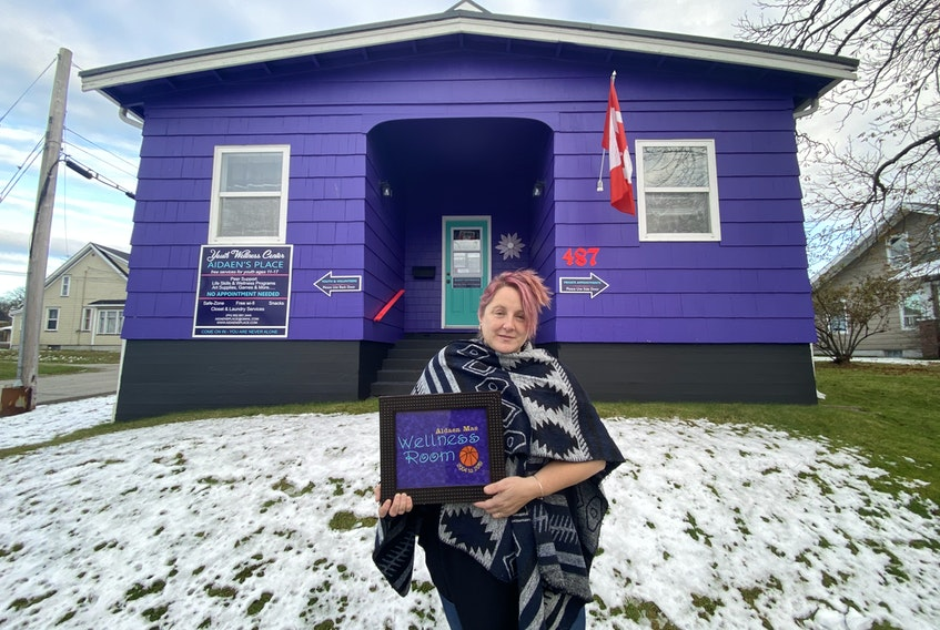 Aidaen's Place founder Kelly Mitchell stands outside the Aidaen's Place Youth Wellness Center at 487 Main St. holding a former Aidaen Mae Wellness Room sign. Aidane's Place is getting $125,000 in funding to buy their current building. TINA COMEAU FILE PHOTO