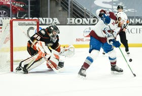 Colorado Avalanche right-winger Liam O'Brien tries to tip the puck past Anaheim Ducks goalie John Gibson  during an NHL game in Anaheim.