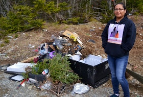 Eskasoni resident Leah Doucette stands next to a pile of garbage near where she picks medicinal plants on Mountain Road. ARDELLE REYNOLDS/CAPE BRETON POST