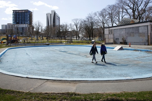 Two people walk across the drained wading pool, at the dated Halifax Commons swimming facility Thursday, April 8, 2021.