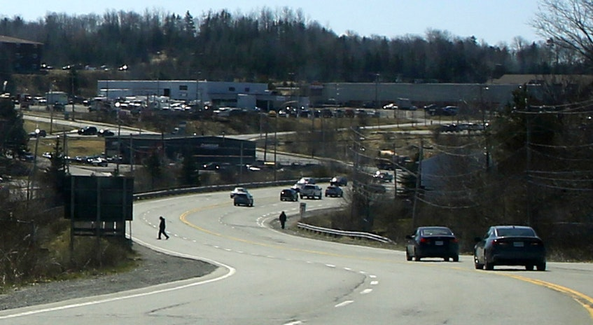 A man crosses Beaver Bank Road not far from the Beaver Bank Connector, in Lower Sackville Thursday, April 15, 2021. Local residents use a path, seen at lower right, to access the nearby transit terminal after walking through lanes of traffic. - Tim  Krochak