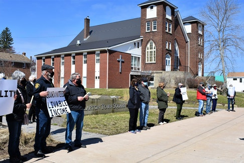 Vigil participants in Stellarton hold signs which clearly state their ask of the federal Liberal Party, to help address poverty across Canada.