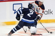 Edmonton Oilers centre Connor McDavid (right) is lined up by Winnipeg Jets defenceman Dylan DeMelo in Winnipeg on Tues., Jan. 26, 2021.