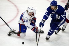 Laval Rocket's Cole Caufield, left, fights for control of the puck with Toronto Marlies' Teemu Kivihalme at Toronto's Coca-Cola Coliseum on April 9, 2021.