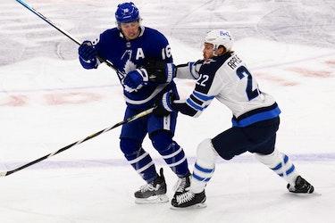 Toronto Maple Leafs forward Mitchell Marner tries to avoid a check from Winnipeg Jets forward Mason Appleton on Thursday night.