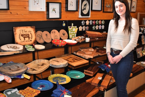 Nineteen-year-old Rileigh Conrod beside her wood burning artwork on sale at the Totally Local in downtown Truro.